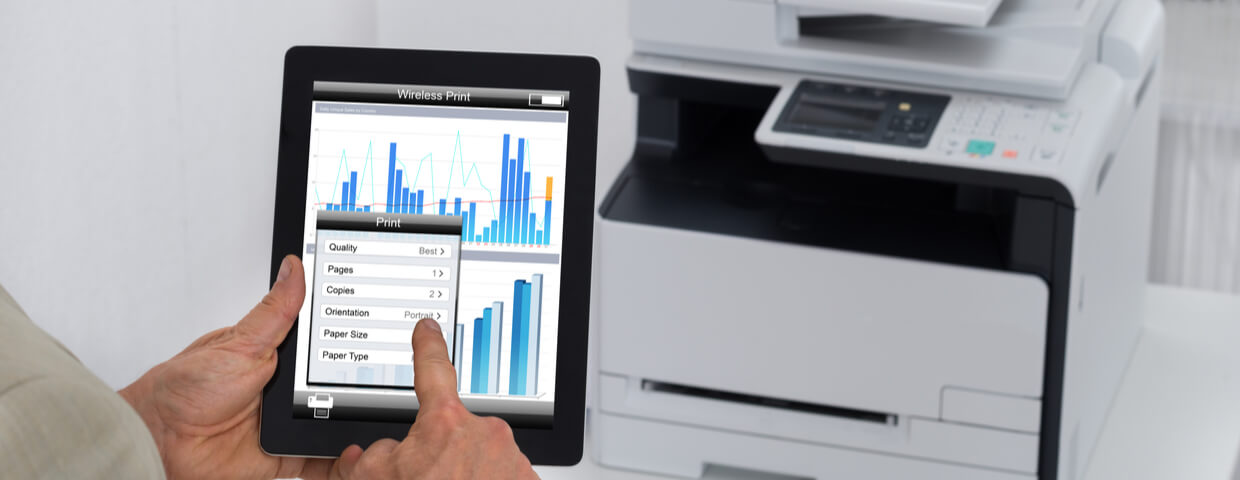 Cropped image of businessman giving print command on digital tablet in office
